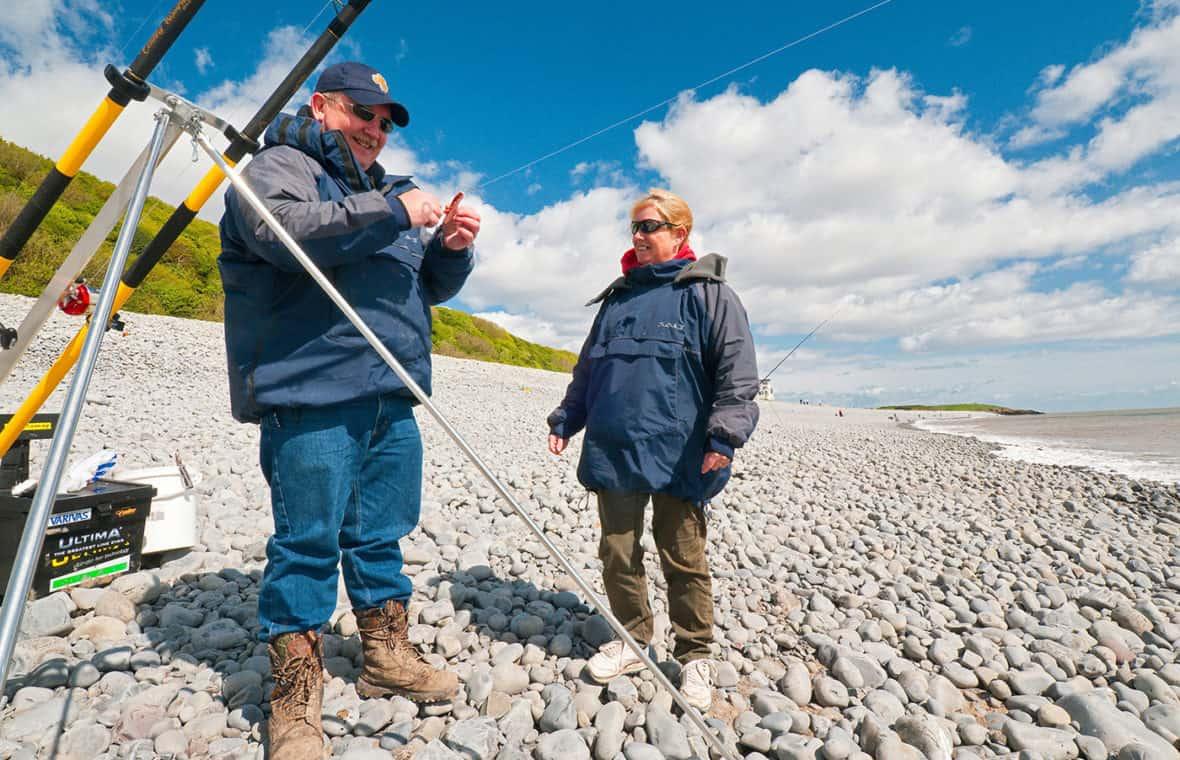 Two people fishing on Knap beach